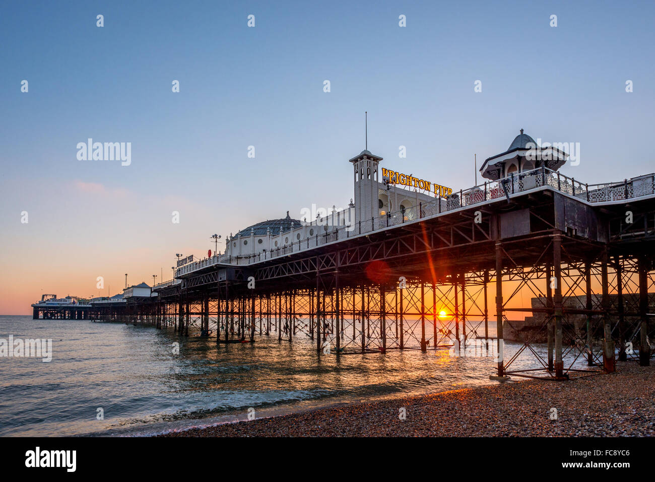 The sun sets on the horizon behind the Palace Pier, Brighton. - Stock Image