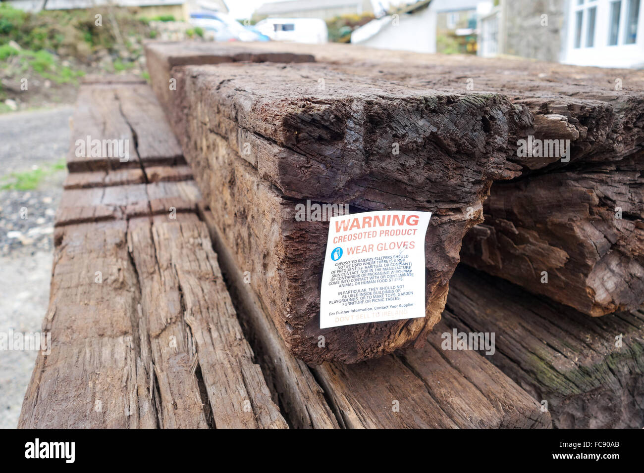 A sign on creosoted wooden railway sleepers advising caution and warning to wear gloves when handling and do not - Stock Image