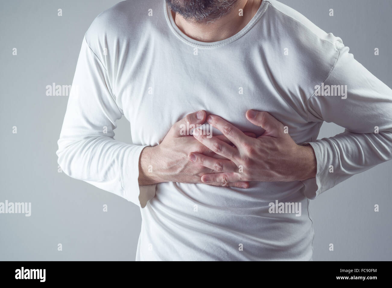Severe heartache, man suffering from chest pain, having heart attack or painful cramps, pressing on chest, painful - Stock Image