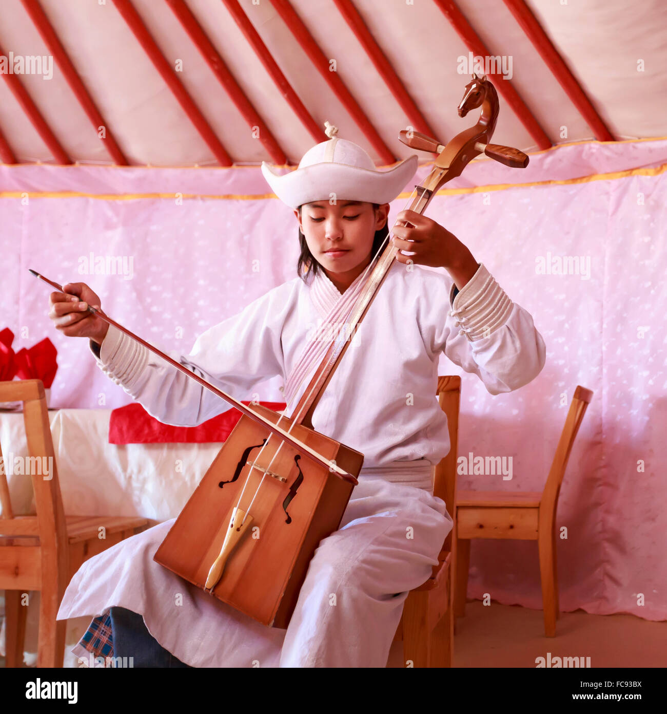 Young man in traditional dress plays horse head fiddle in a ger, Gobi Desert, Mongolia, Central Asia - Stock Image