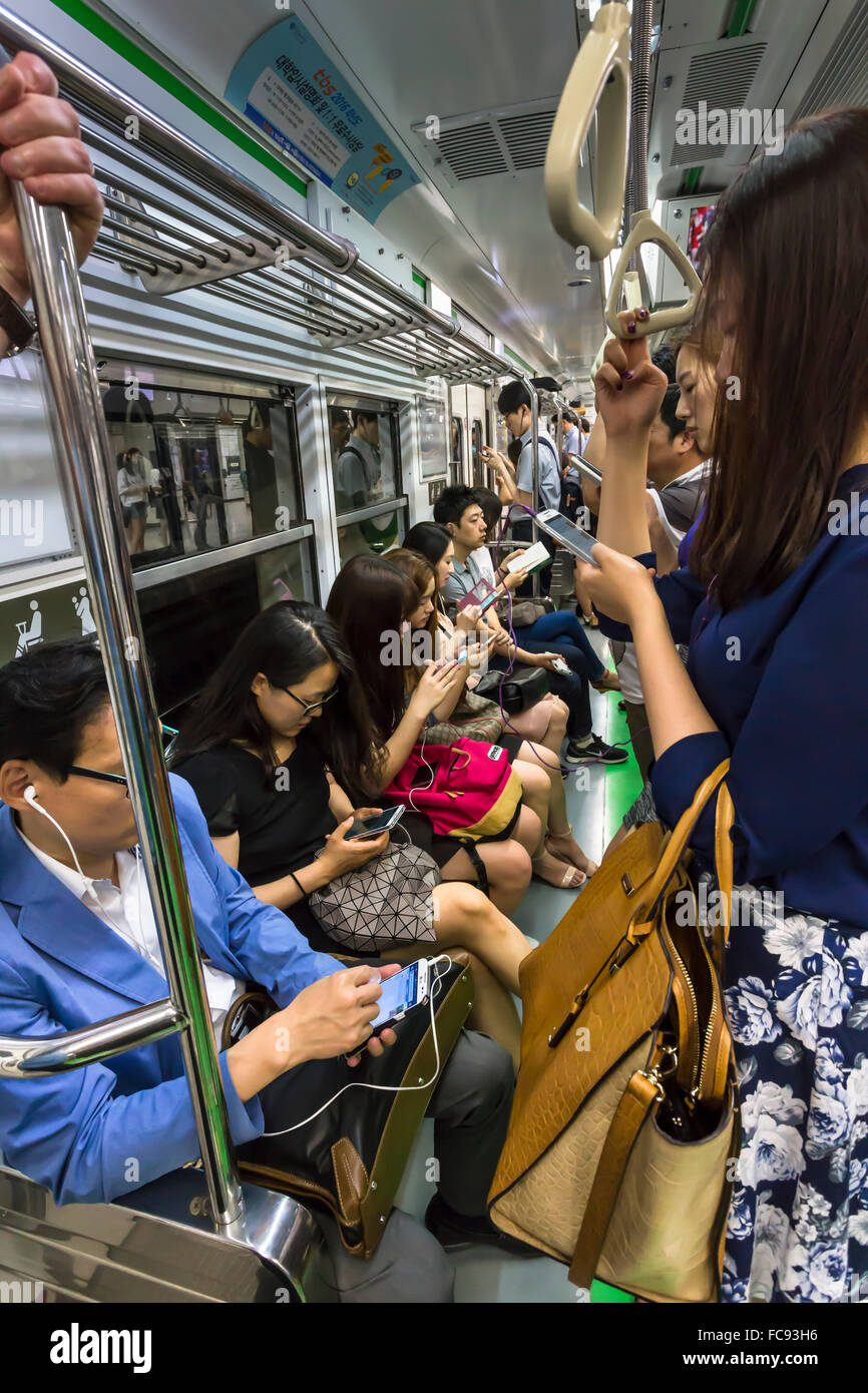 Smartly dressed commuters on the busy subway looking at their phones and e-devices, Seoul, South Korea, Asia - Stock Image