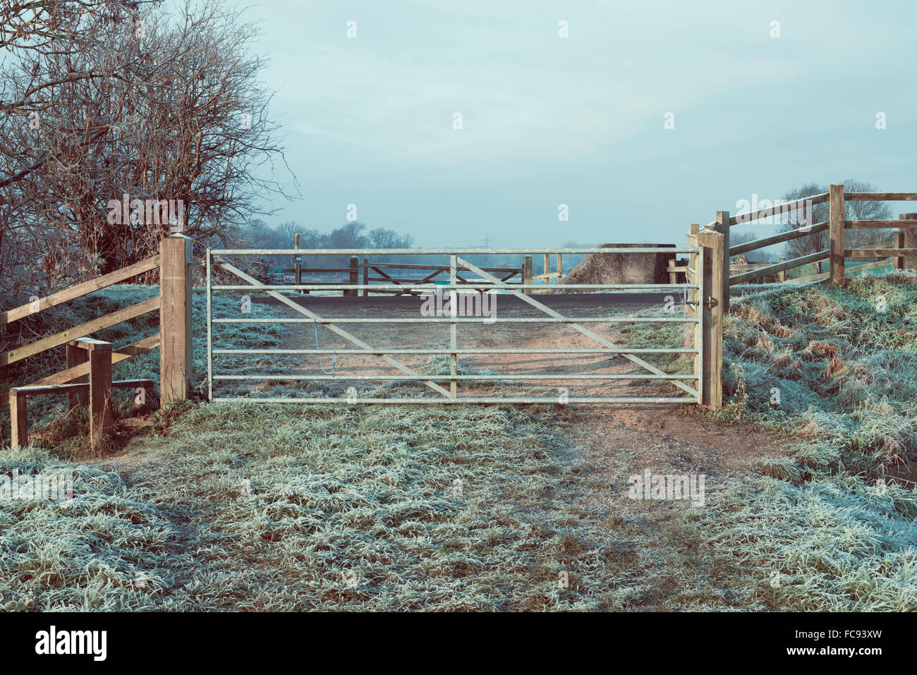 Metal farm gate with stile at end of farm track in the winter with frost on the ground - Stock Image
