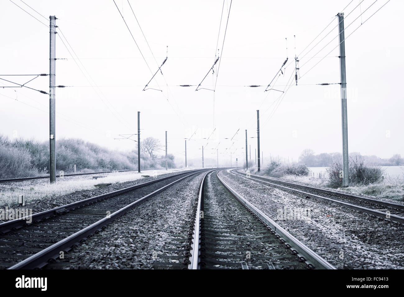 Perspective view down the train tracks into the distance on an frosty morning. Ice on the tracks and overhead cables - Stock Image
