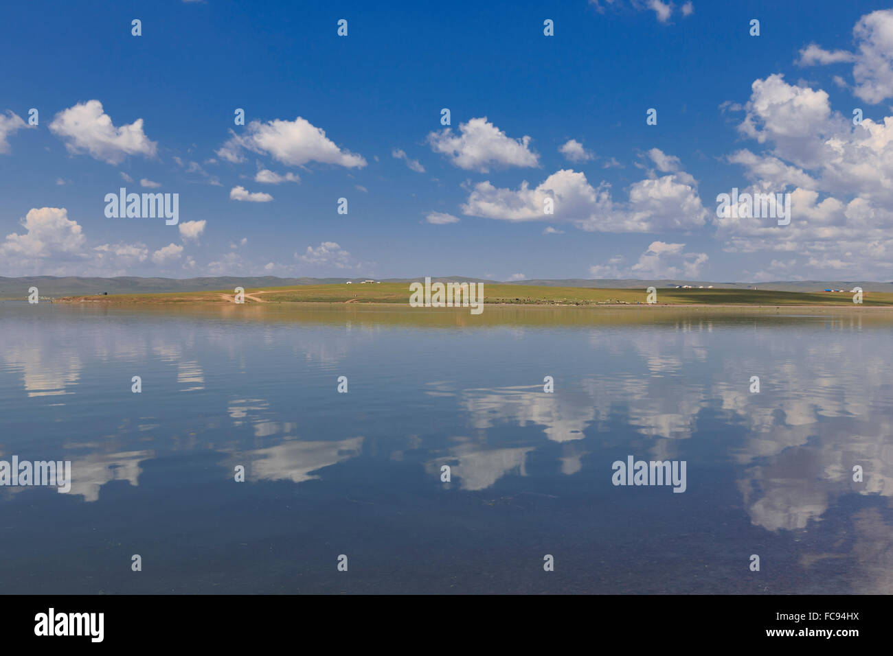 Fluffy clouds in a blue summer sky, reflected in a lake, distant reflected gers, Arkhangai, Central Mongolia,Central - Stock Image