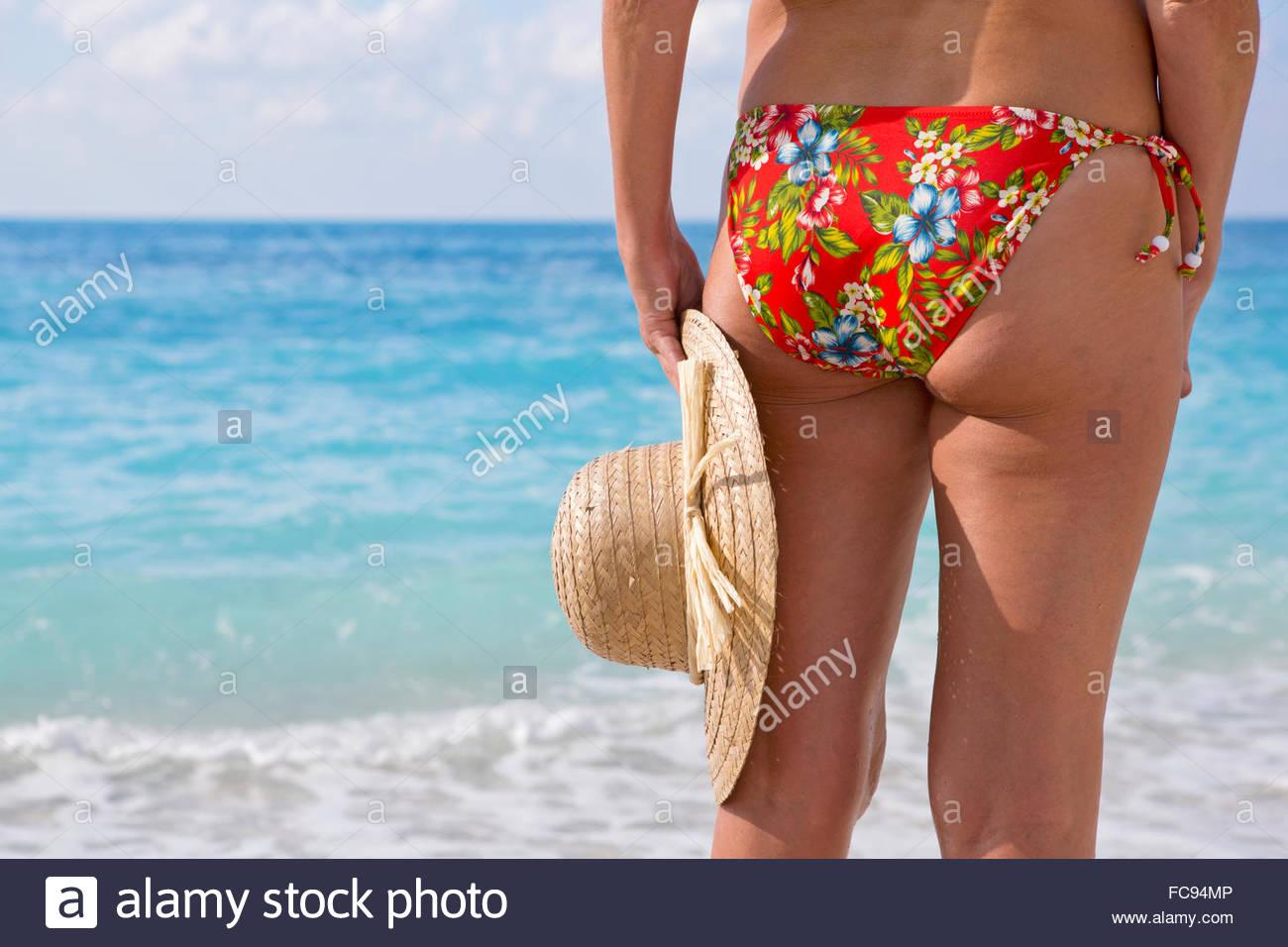 Close up woman in bikini holding sun hat at ocean - Stock Image