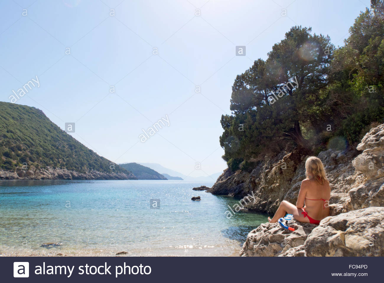 Woman in bikini sitting on rocks on sunny beach - Stock Image