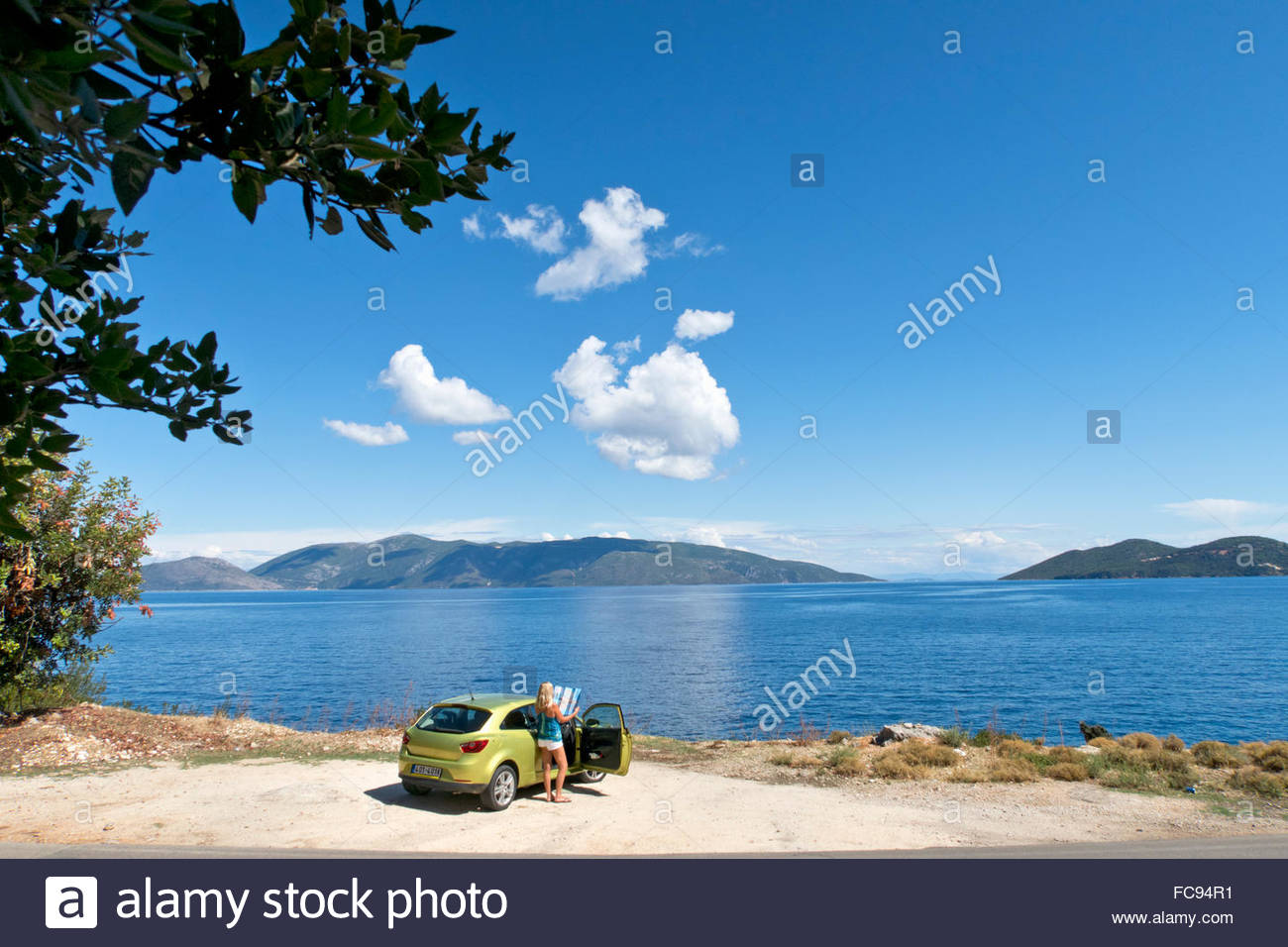 Woman with map next to car at sunny oceanside Stock Photo