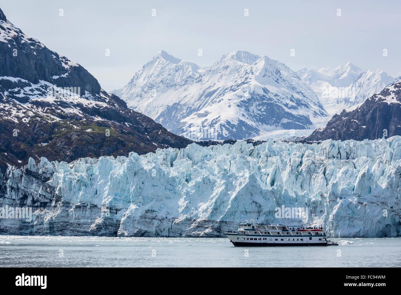 A tourist ship explores the Lamplugh Glacier in Glacier Bay National Park and Preserve, southeast Alaska, USA - Stock Image