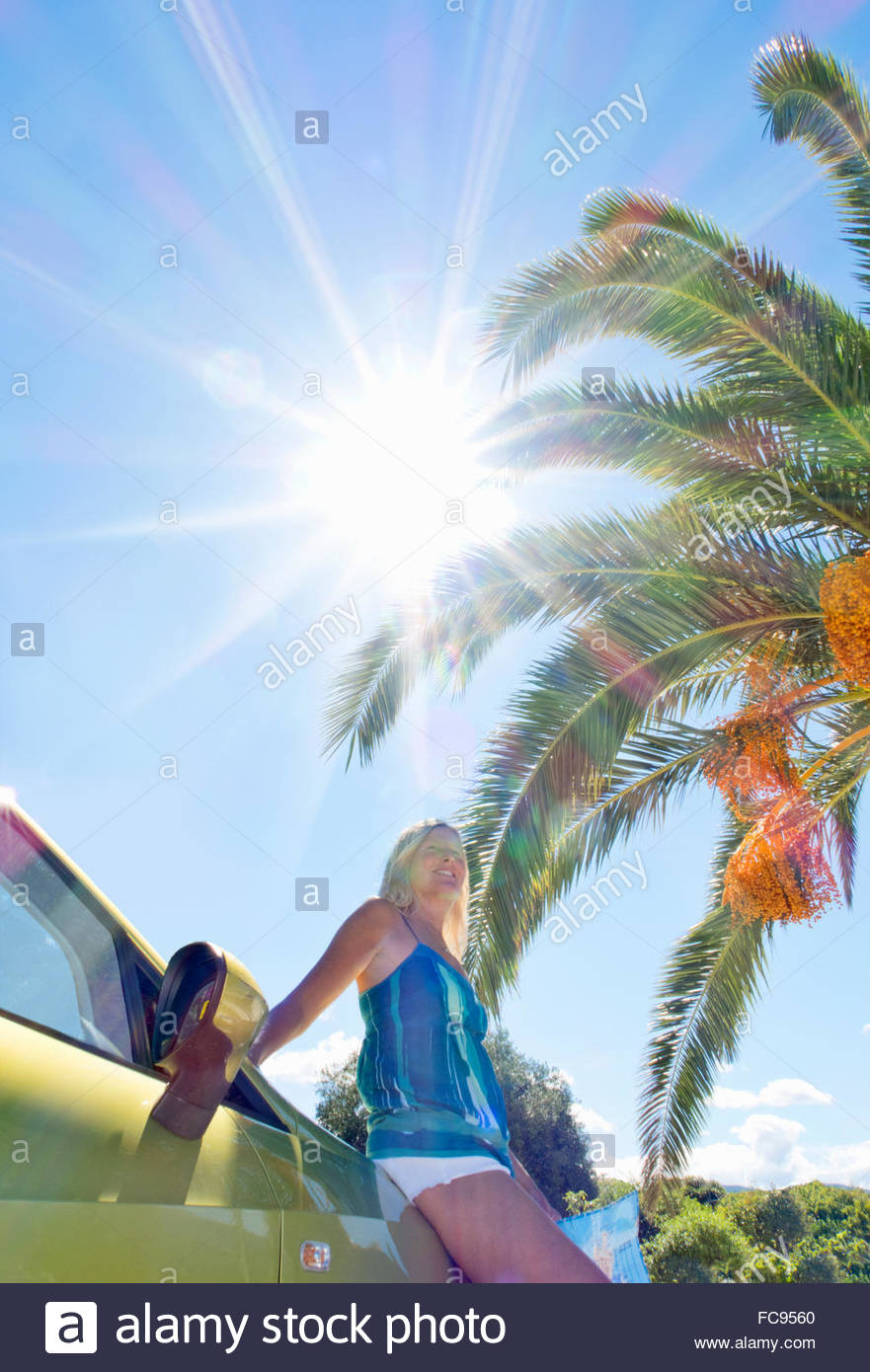 Smiling woman leaning on car under palm tree and sun in blue sky - Stock Image