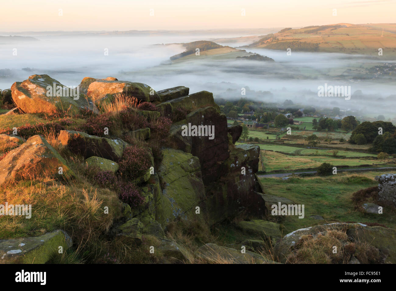 Mist folds over Curbar village, fields and woods from Curbar Edge with heather, Peak District, Derbyshire, England, - Stock Image