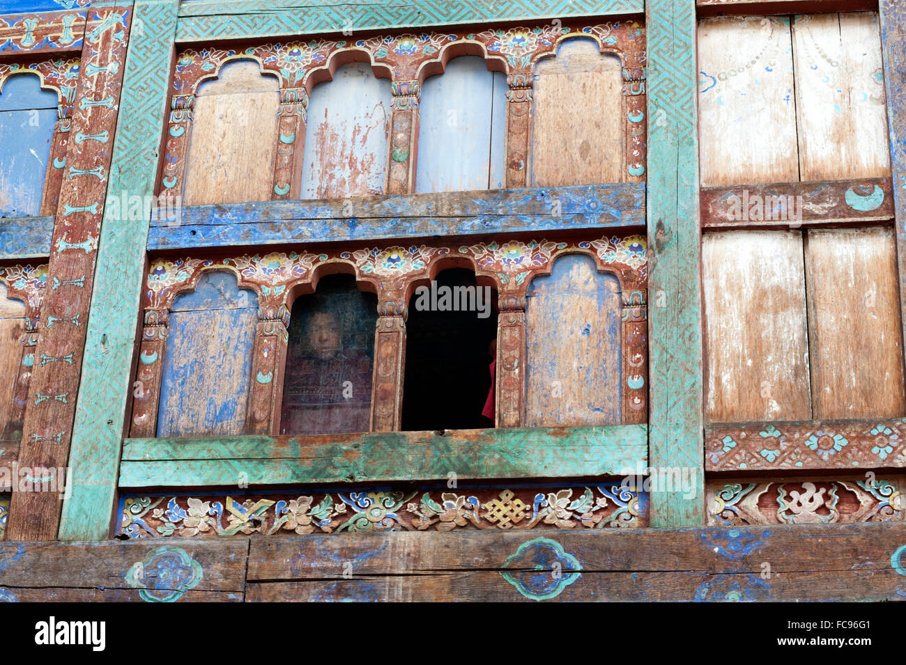 Monk looking out of window with fading blue paint in Wangdue Chhoeling Palace, in need of restoration, Bumthang, - Stock Image