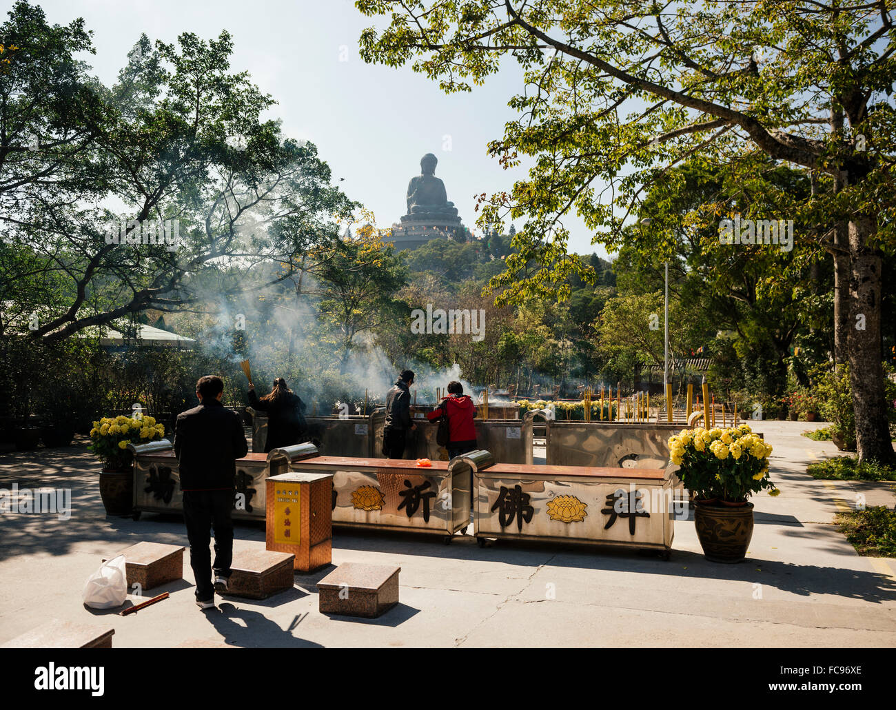 People lighting incense at Po Lin Monastery with Big Buddha statue in background, Lantau Island, Hong Kong, China, - Stock Image