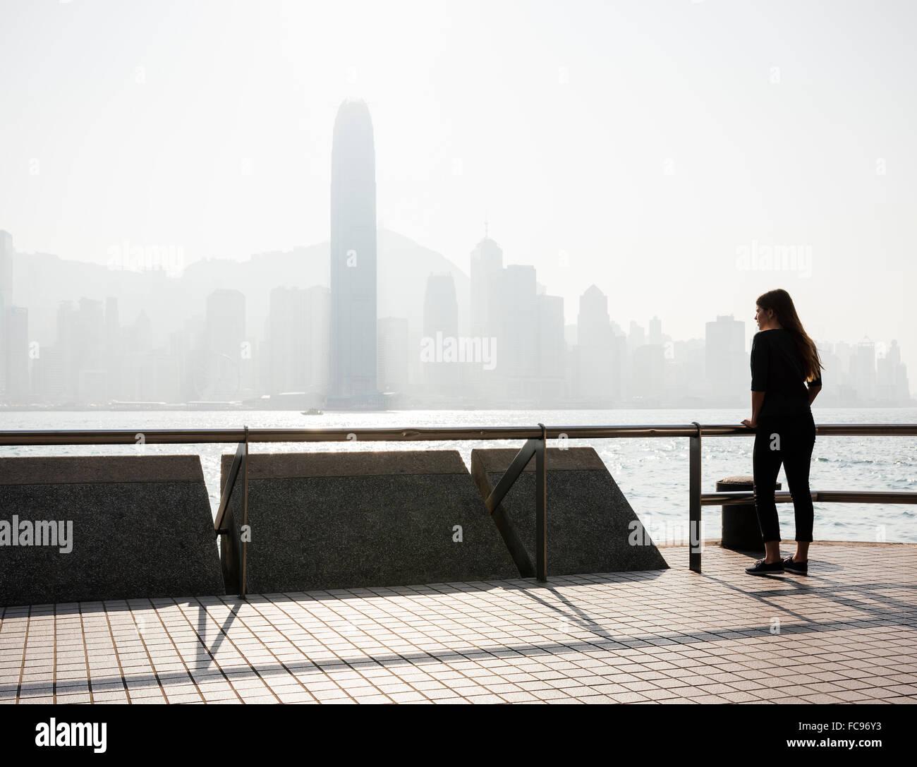 Young woman standing on Tsim Sha Tsui Waterfront, Kowloon, Hong Kong, China, Asia - Stock Image