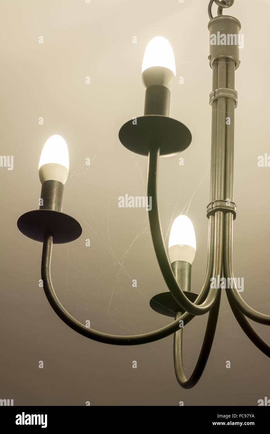 dust webs attached to light fitting prior to dusting - Stock Image