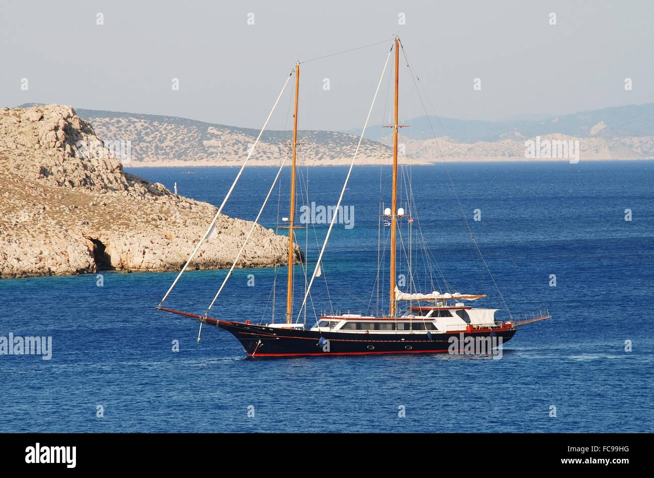 A twin masted yacht entering Emborio harbour on the Greek island of Halki. Stock Photo
