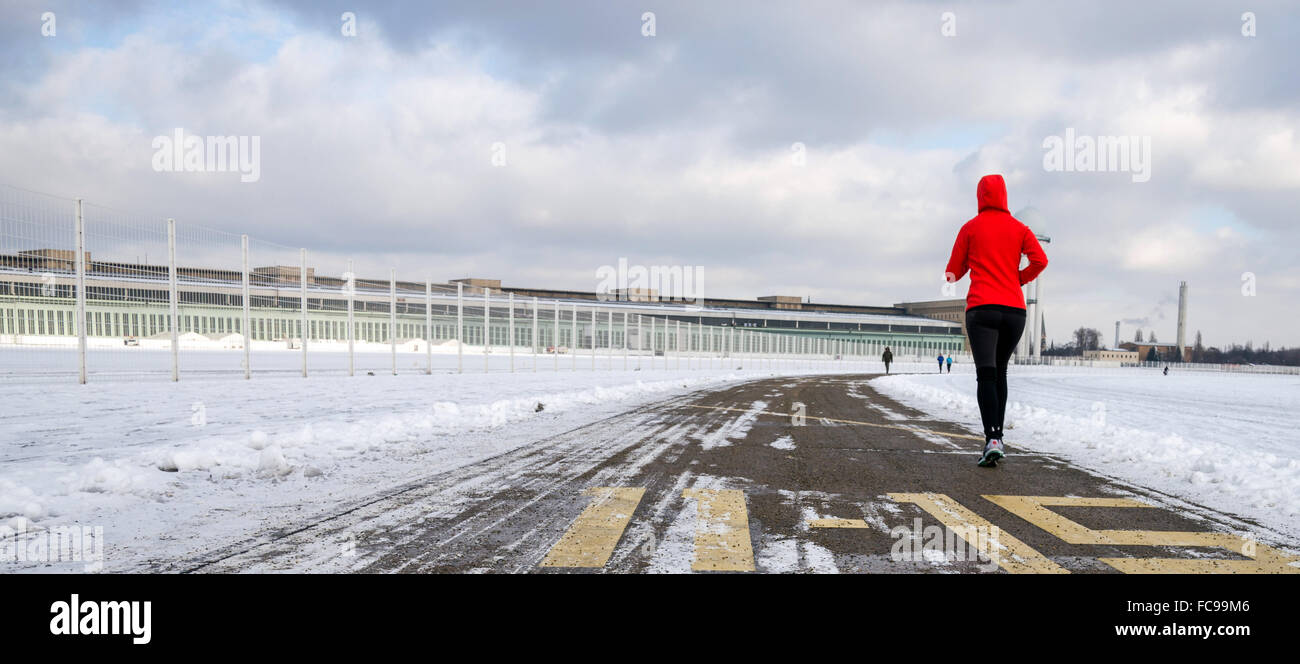 A woman jogging in front of the hangars of the former Tempelhof Airport in Berlin, Germanym, 20 Janaury 2016. The - Stock Image