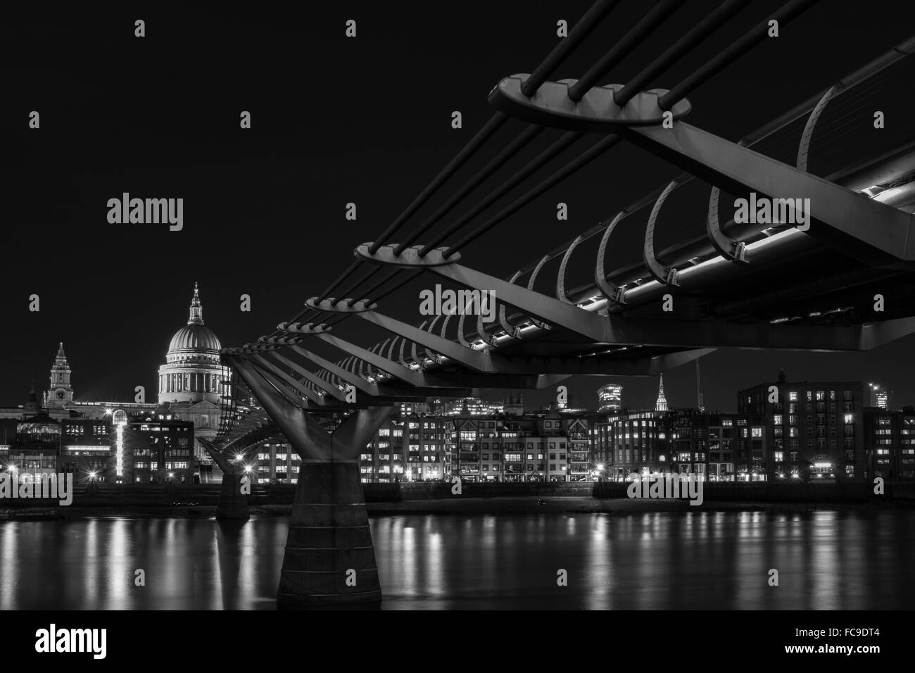 London Black and White urban photography: cityscape of Millennium Bridge, St. Paul's Cathedral and River Thames at night. Stock Photo