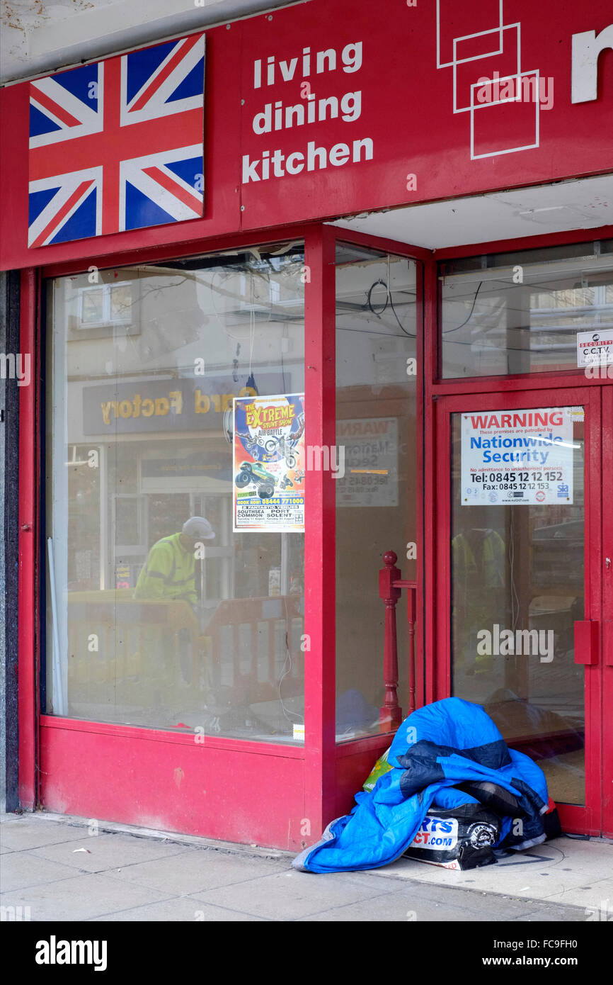 sleeping bags and blankets of homeless people stake out there patch in an empty closed shop doorway england uk - Stock Image