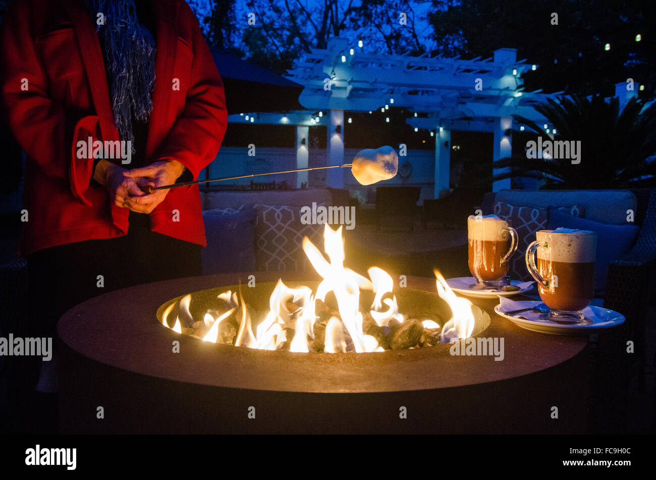 On a cool autumn evening, a woman warms up by a fireplace with s'mores and hot chocolate. - Stock Image