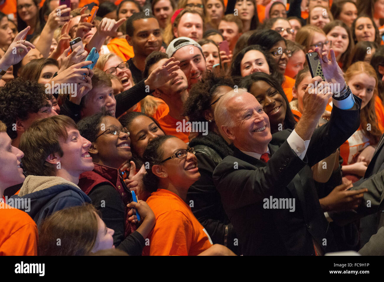 Joe Biden takes a selfie with students after speaking at Syracuse University. - Stock Image