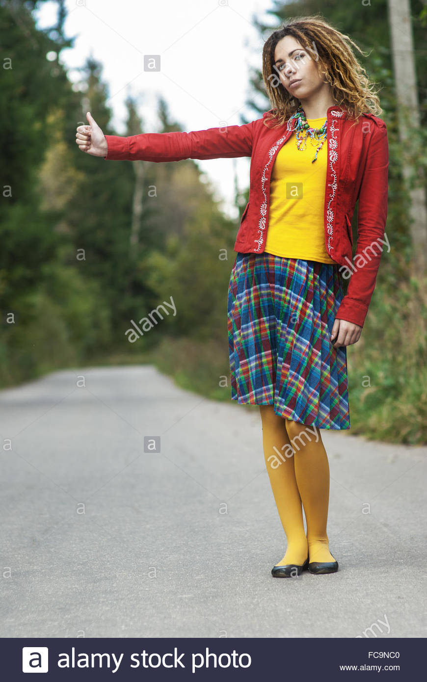 woman with dreadlocks votes hitchhiking - Stock Image