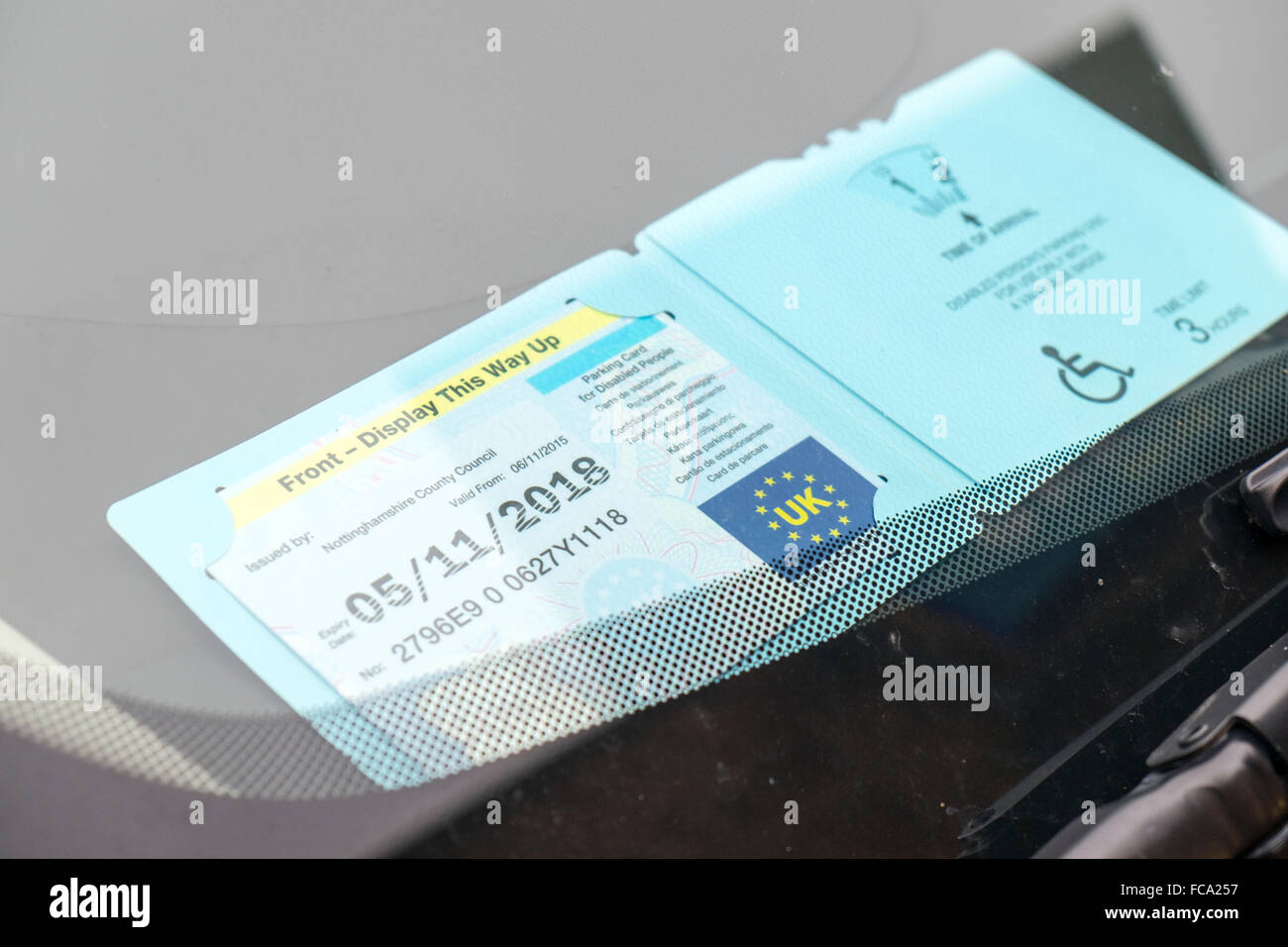 Disabled parking permit badge car park disability space spaces handicapped card blue badge impaired invalid invalidity - Stock Image