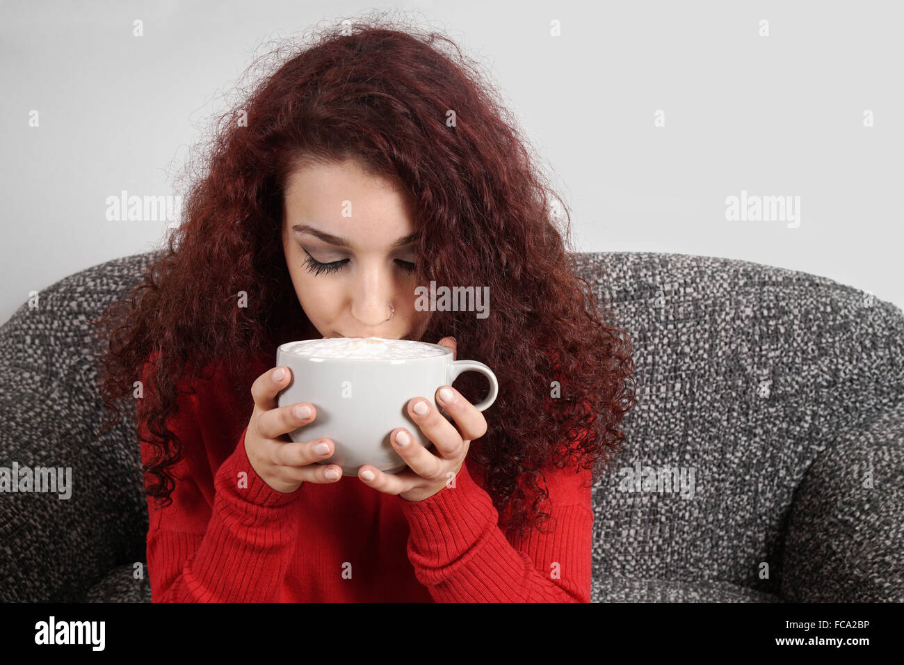 girl sipping from large cup of coffee - Stock Image