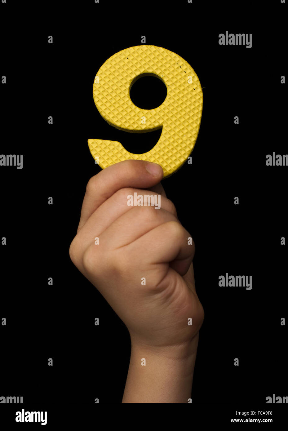 Children hand holding the number Nine - Stock Image