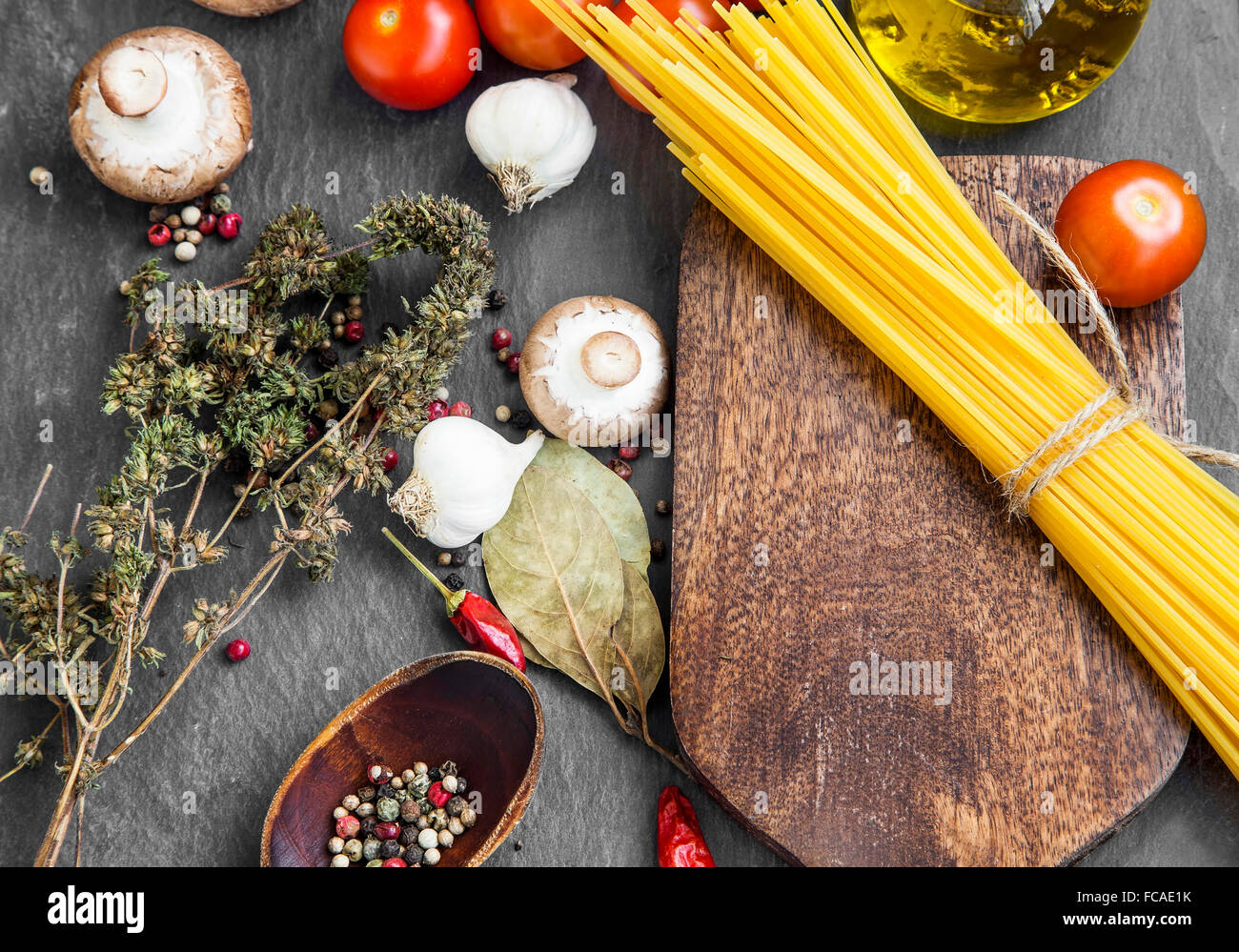 Italian meal ingredients with pasta,spices,tomatoes,olive oil,mushrooms on wooden cutting board - Stock Image