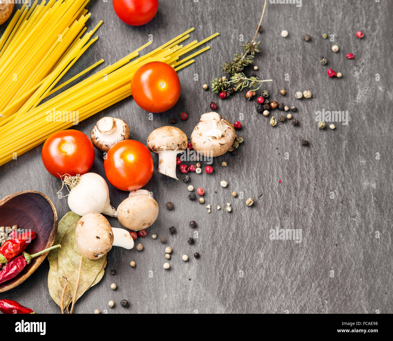 Italian meal ingredients with pasta,spices,tomatoes and mushrooms - Stock Image