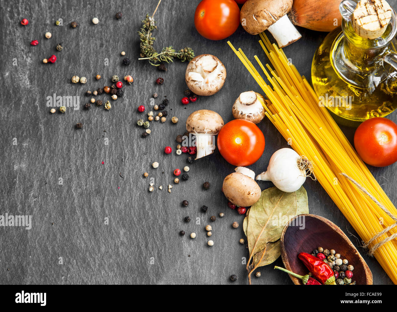 Italian meal ingredients with pasta,spices,tomatoes,olive oil,mushrooms - Stock Image
