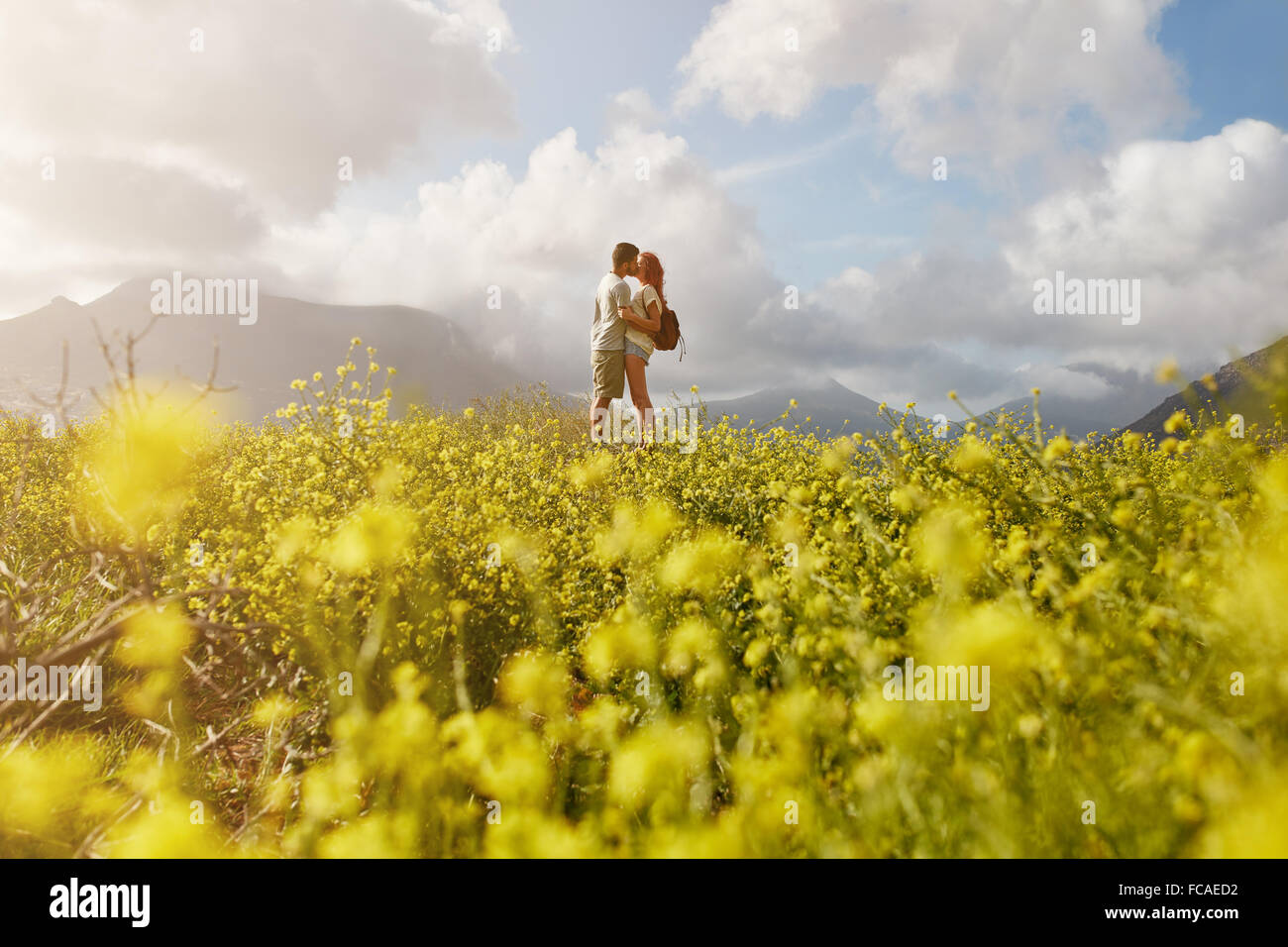 Romantic young couple embracing and kissing on a sunny day outdoors. - Stock Image