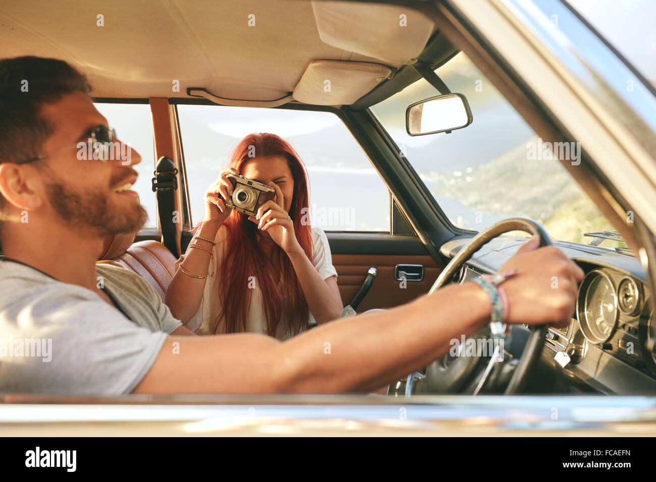 Young couple on a road trip. man driving car with woman taking pictures with retro camera. - Stock Image