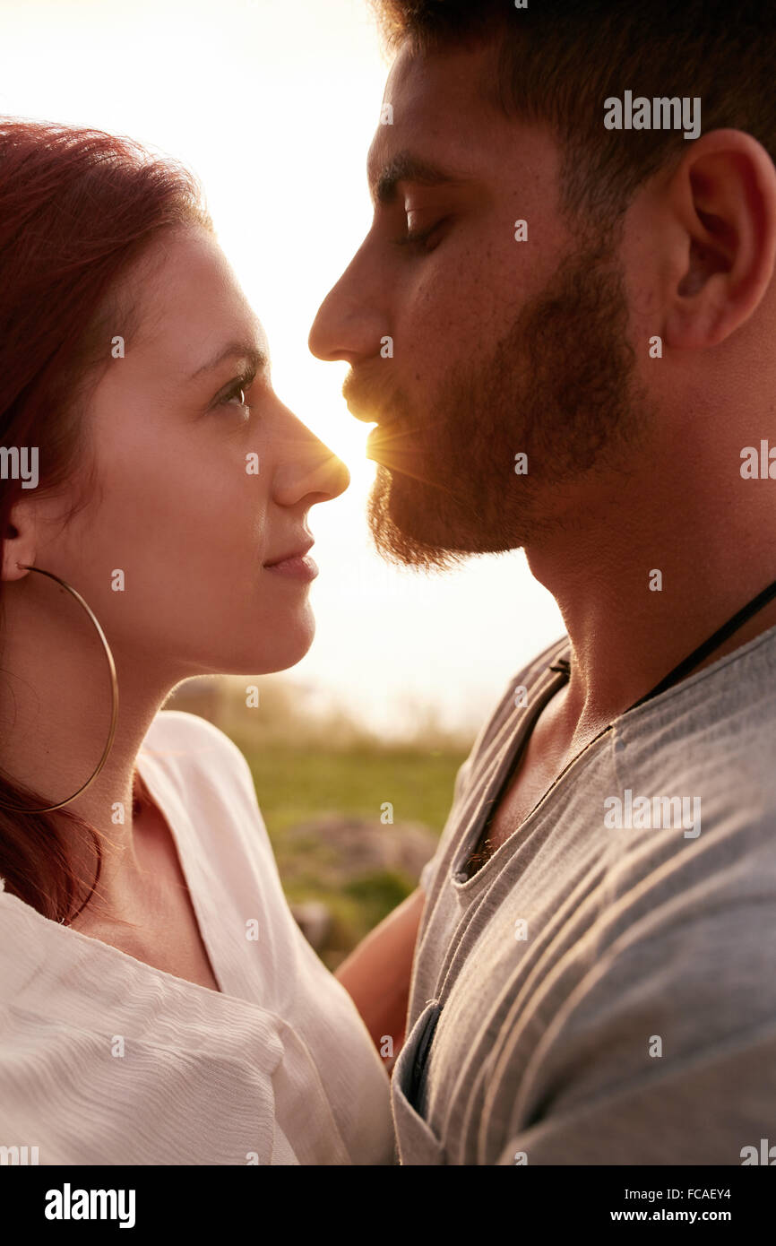 Close up image of young couple in love embracing and looking into each others eyes romantically. Affectionate young - Stock Image