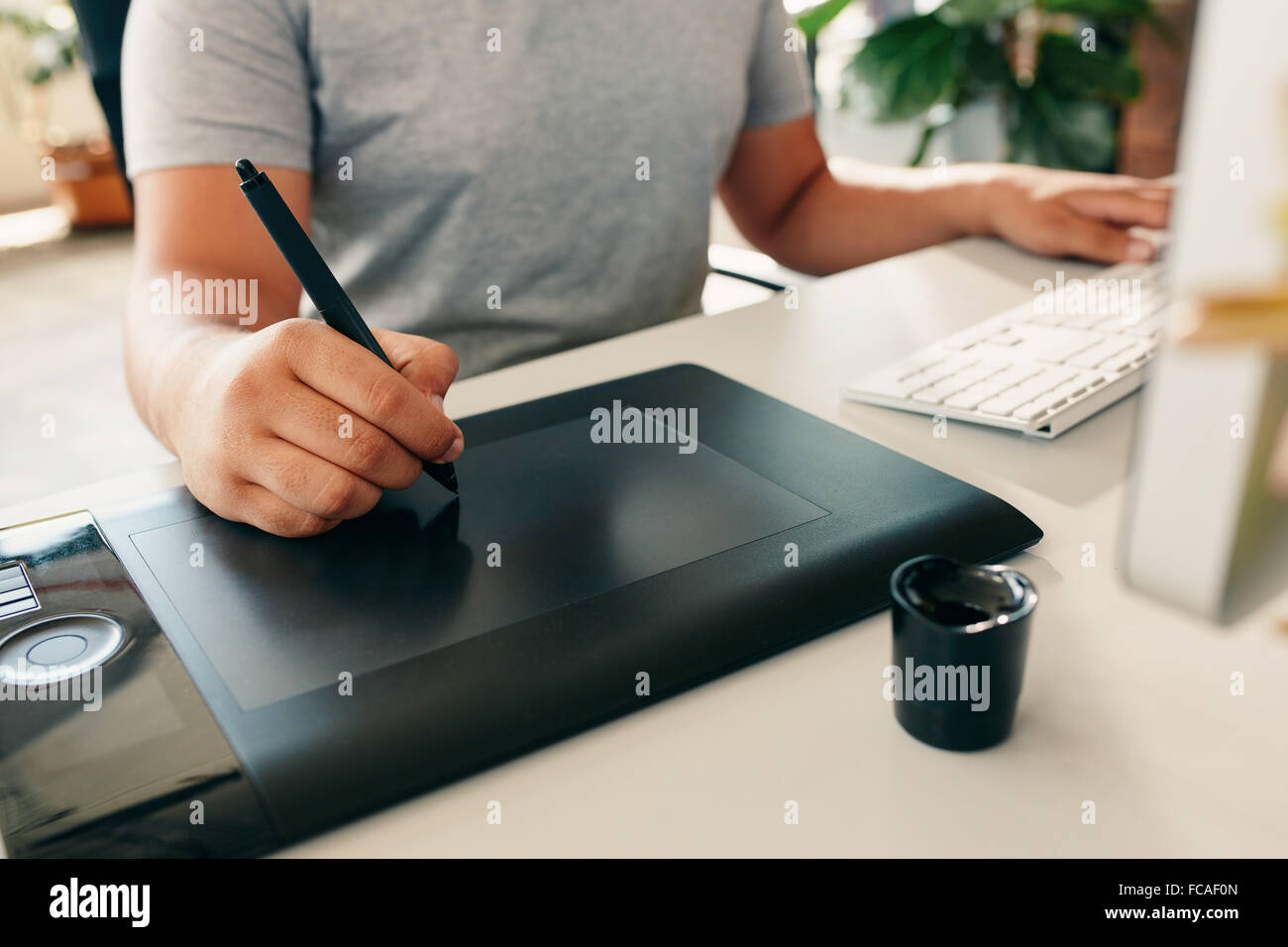 Graphic designer using digital tablet and desktop computer in the office. Close-up of designer's hand working - Stock Image