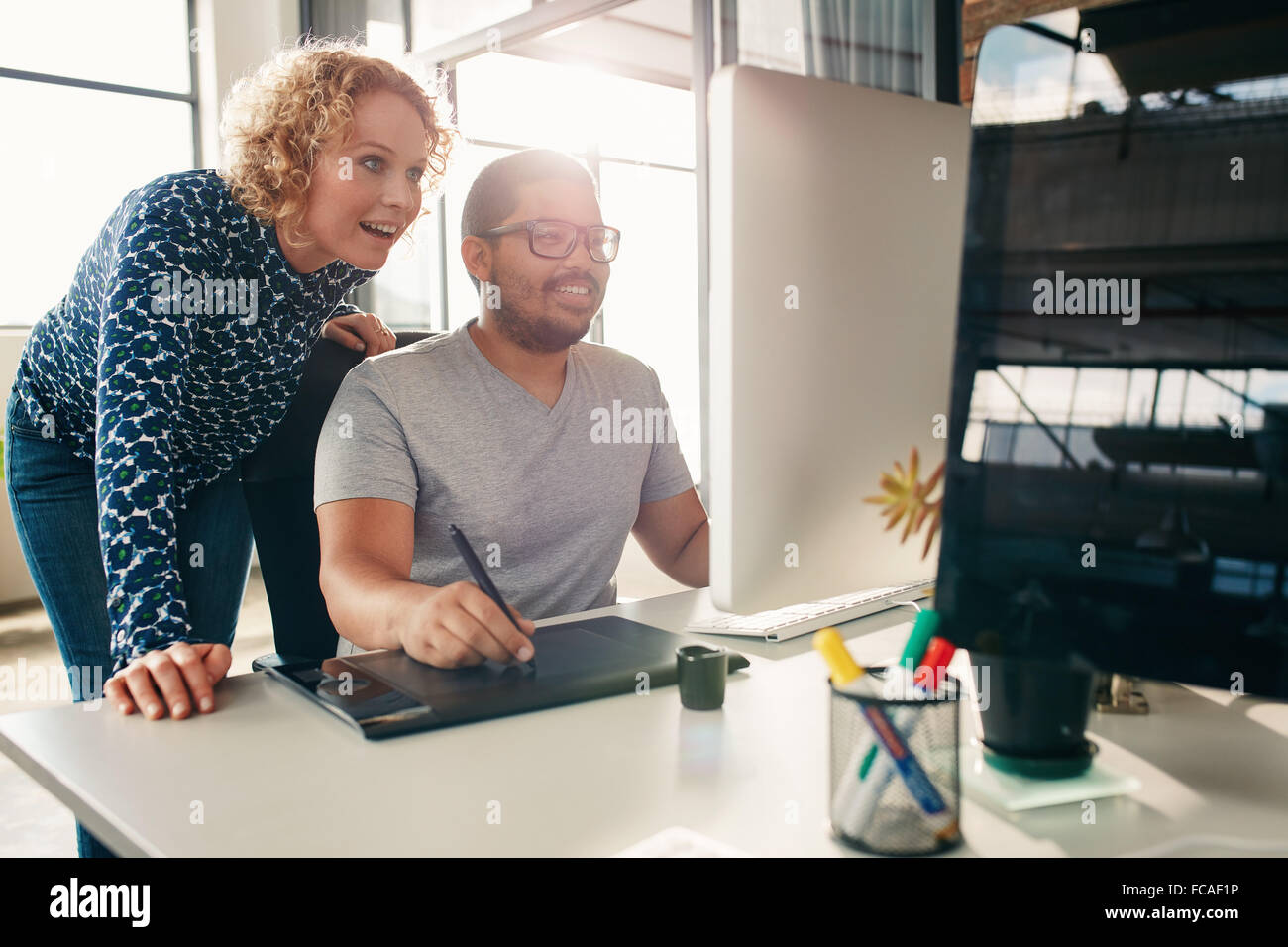 Two young creative people working together on a new project in office. Male and female designer using digital graphic - Stock Image