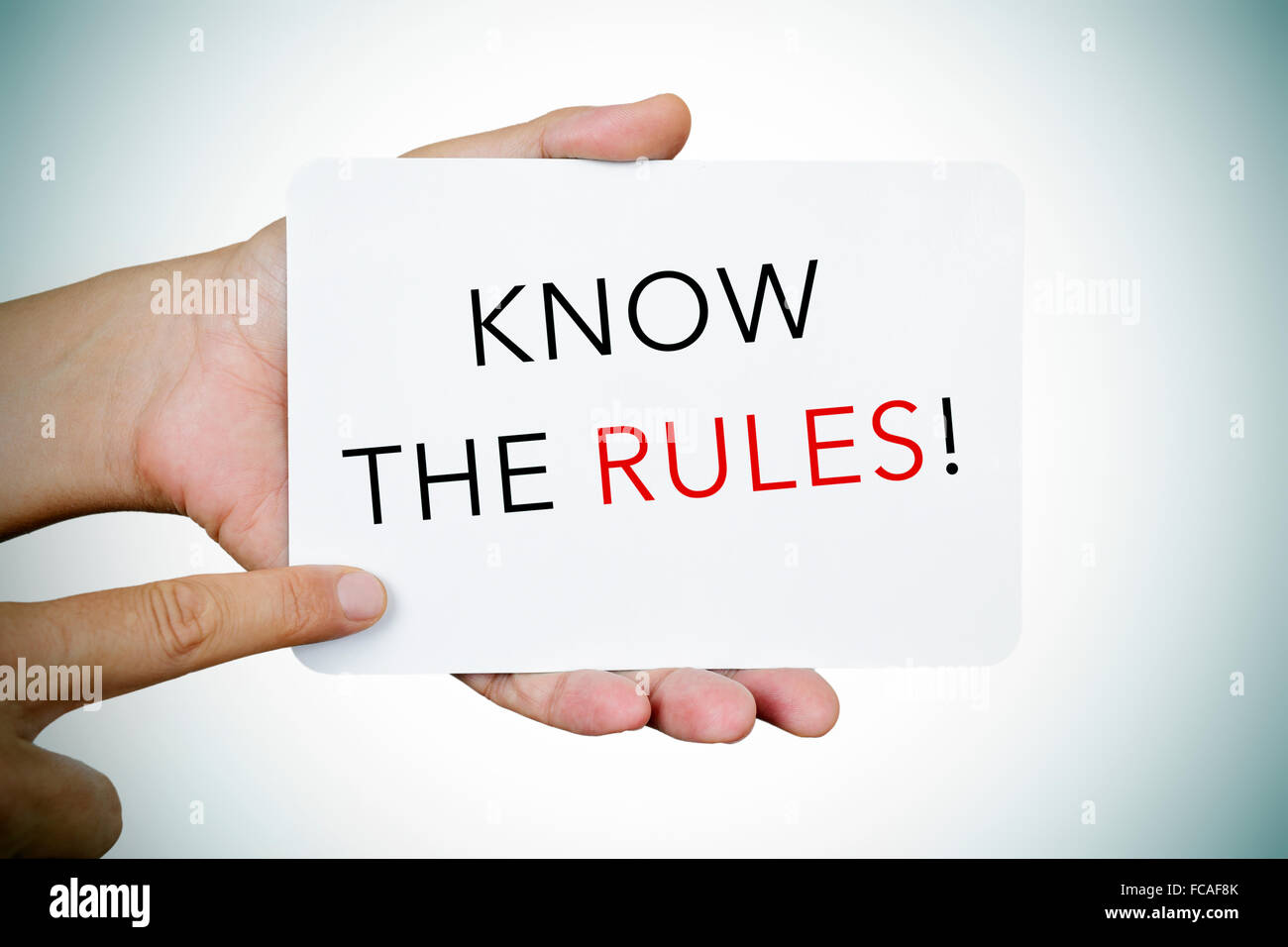 closeup of the hands of a young man showing a signboard with the text know the rules - Stock Image