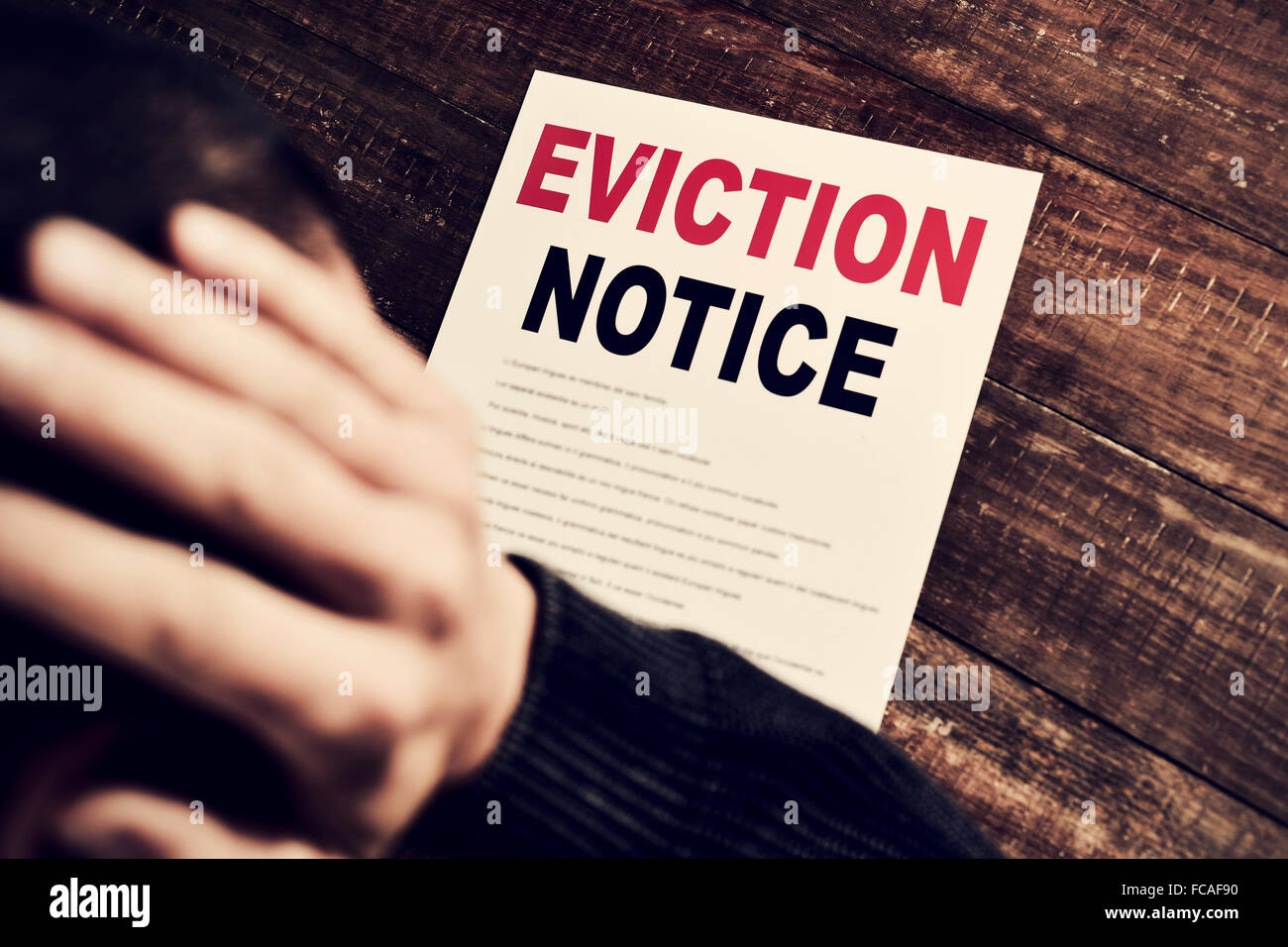 a young caucasian man with his hands in his head concerned because has just received an eviction notice - Stock Image