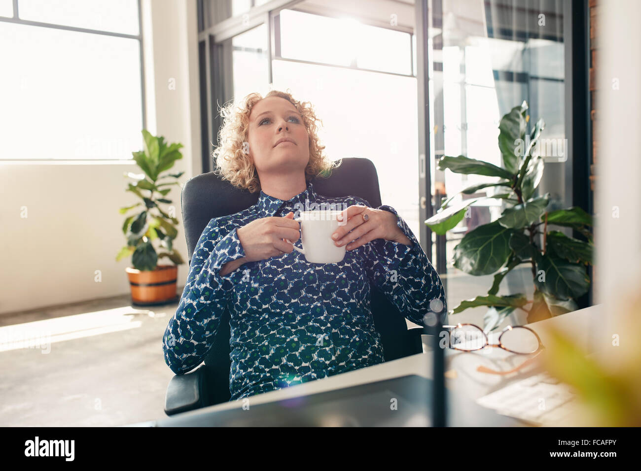 Businesswoman sitting at her desk in office with a cup of coffee looking away and thinking. - Stock Image