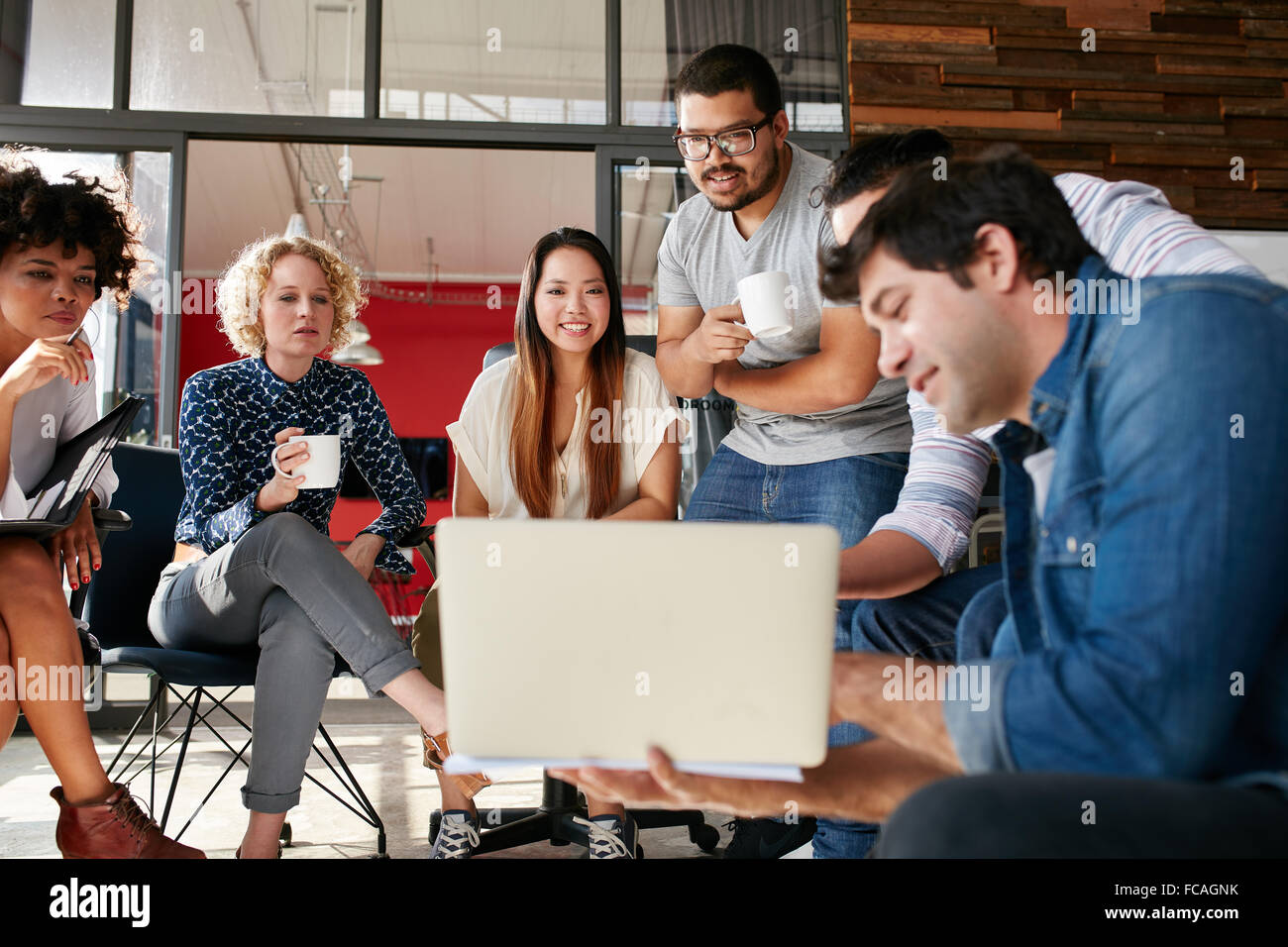 Team of creative people looking at colleague showing project plan on his laptop. Diverse group of young people having - Stock Image