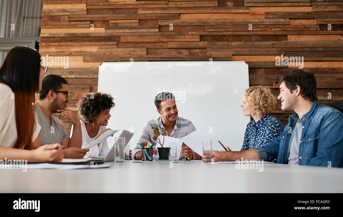 Group of happy young business people meeting in conference room. Team of creative professionals discussing new project. - Stock Image