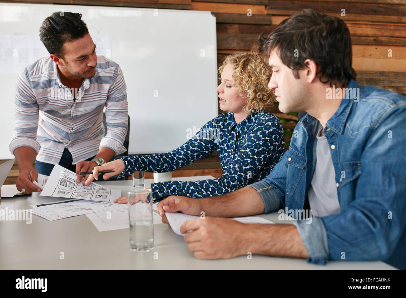 Young man and woman doing discussion at table during a meeting in office. Creative team planning new business strategy. - Stock Image