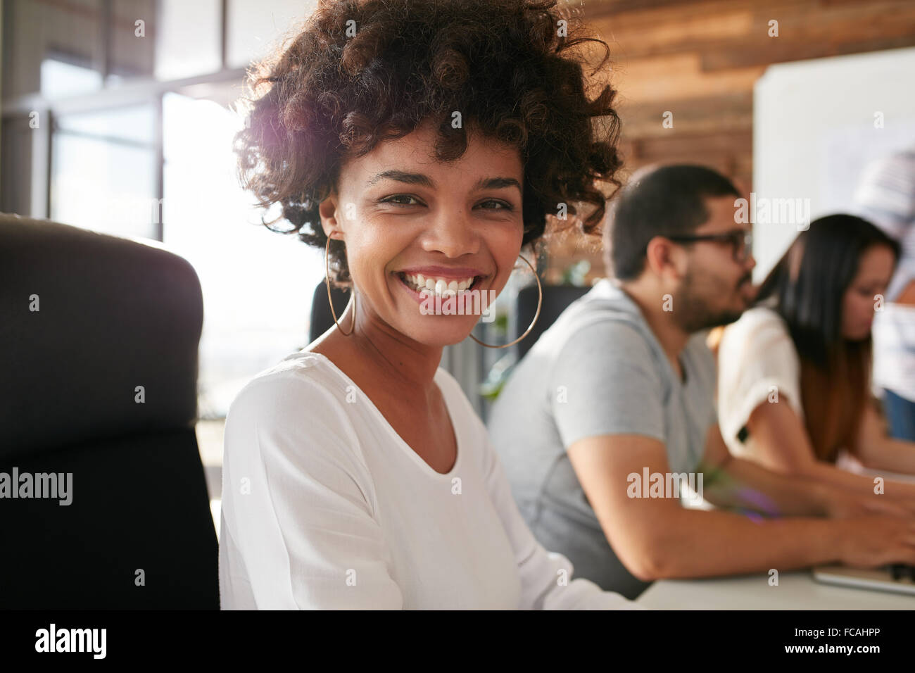Closeup portrait of cheerful young african woman sitting in conference room with coworkers in background. Creative - Stock Image