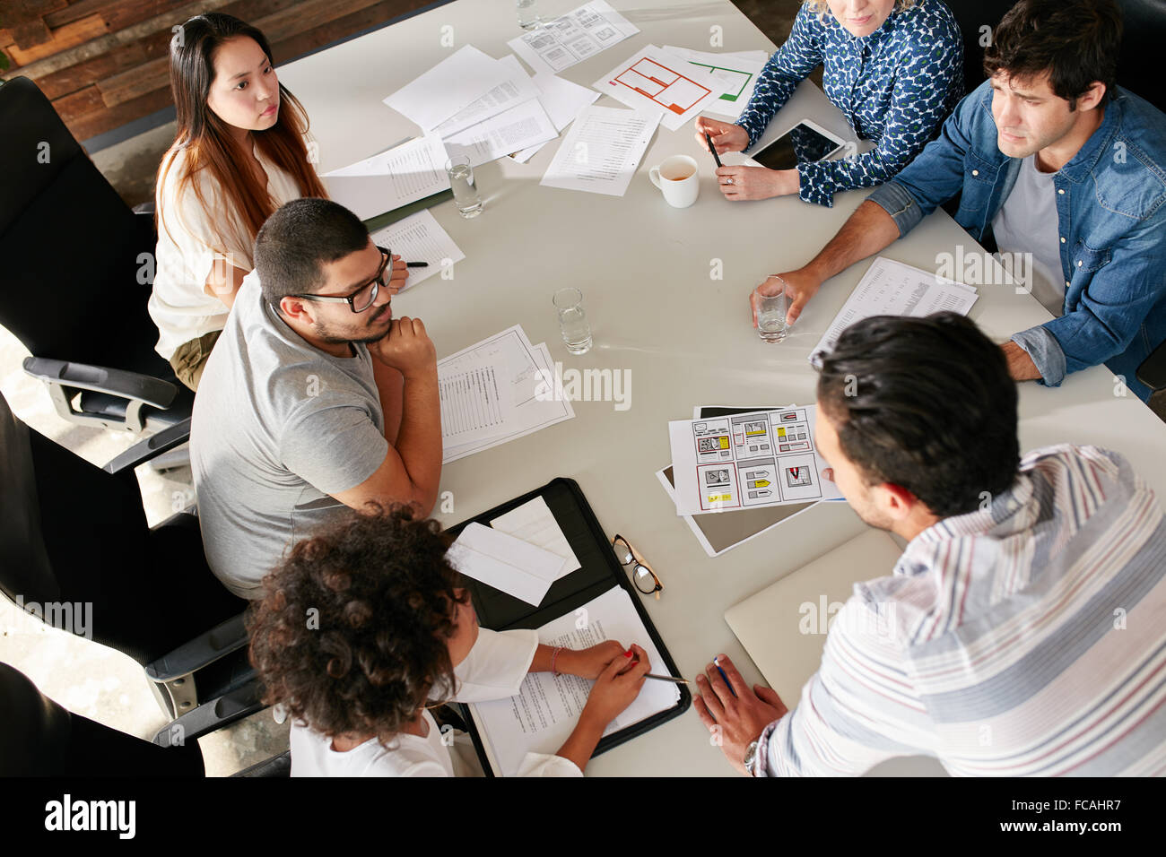 High angle view of creative team sitting around table discussing business ideas. Mixed race team of creative professionals - Stock Image