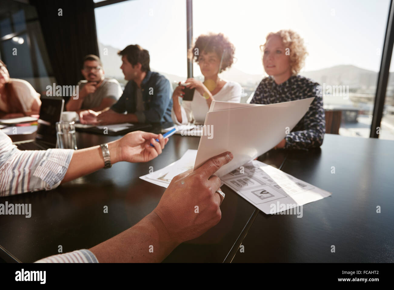 Papers in hands of young man explaining business plan to his creative team. Creative professionals meeting in office. - Stock Image