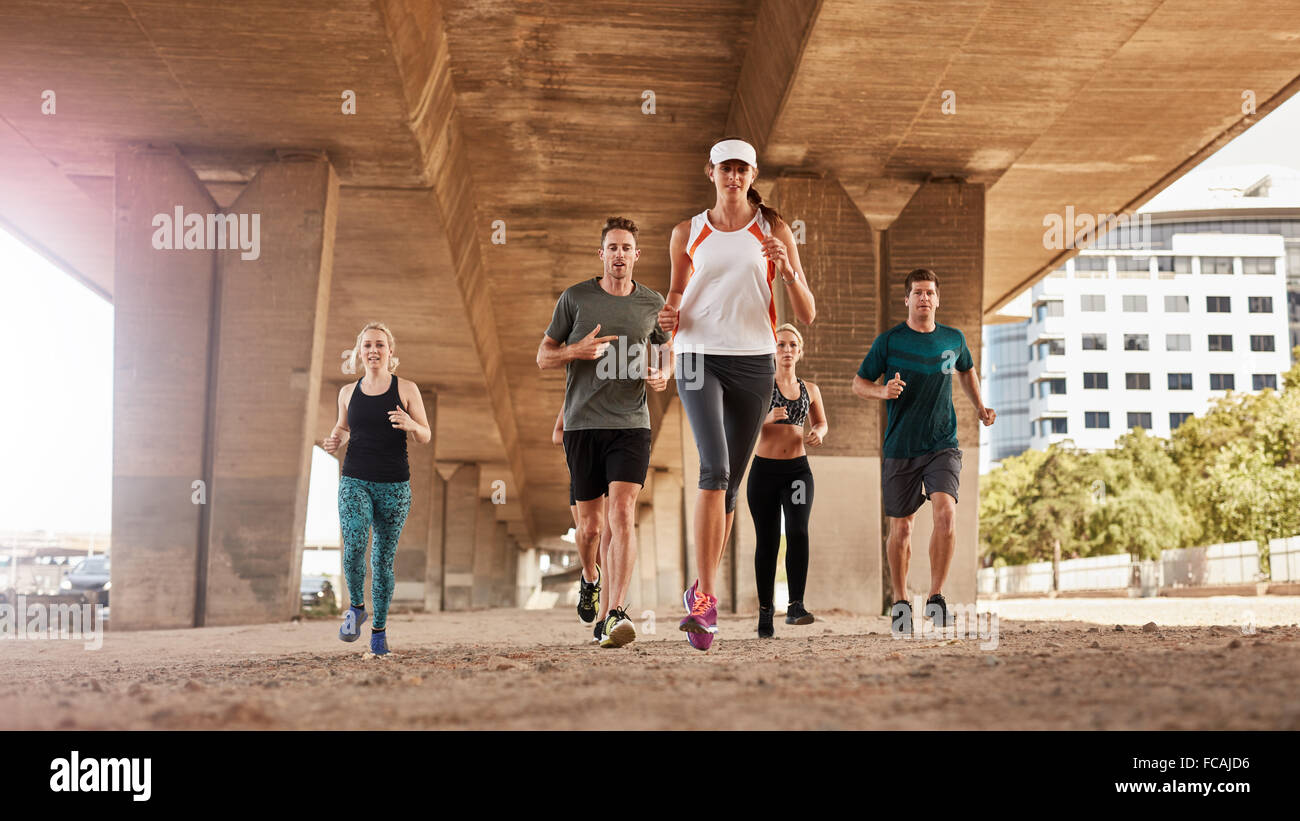 Portrait of group of young people in sports clothing running under a bridge through the city. Running club members - Stock Image