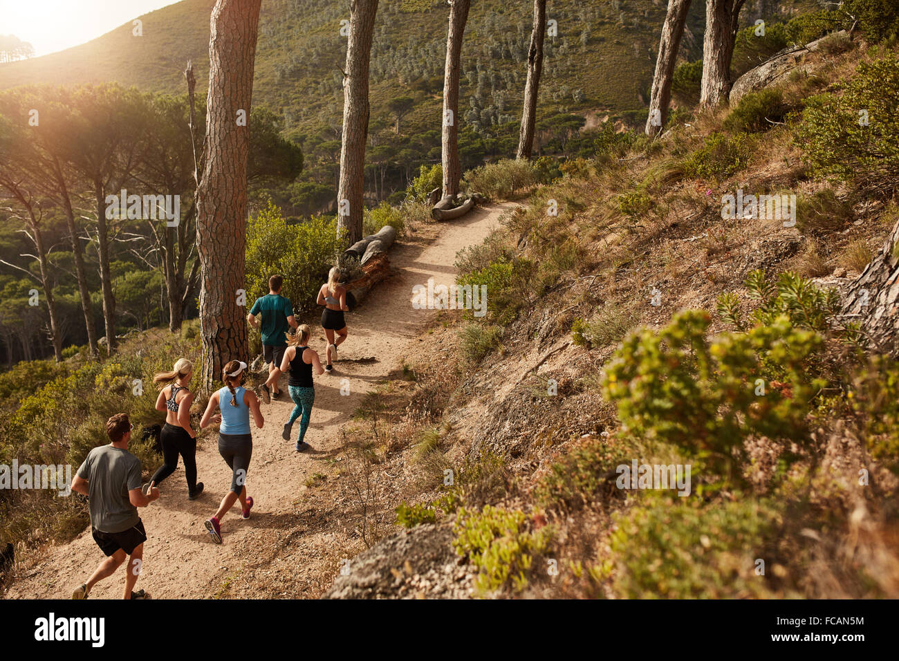 Group of young people trail running on a mountain path. Runners working out in beautiful nature. - Stock Image