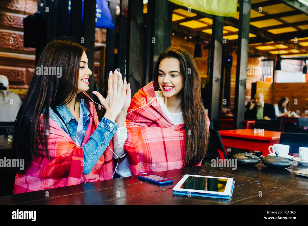 Two young and beautiful girls having fun in cafe - Stock Image