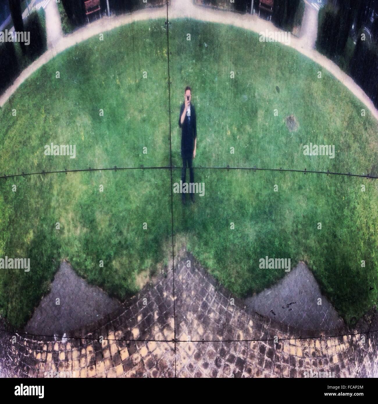 Man On Lawn Through Fisheye Lens - Stock Image
