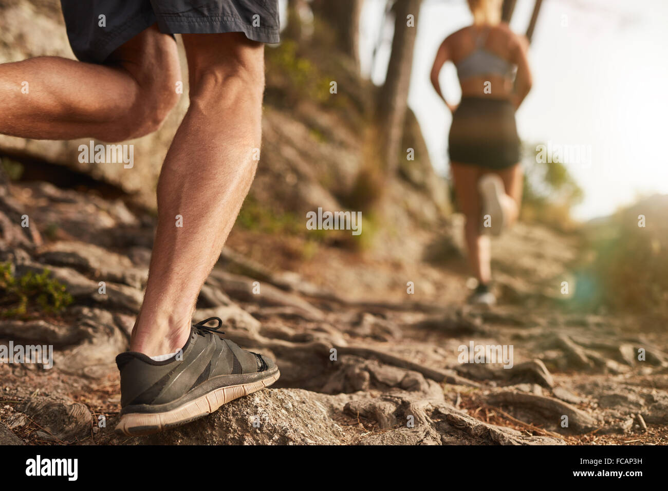 Closeup of male feet run through rocky terrain. Cross country running with focus on runner's legs. - Stock Image